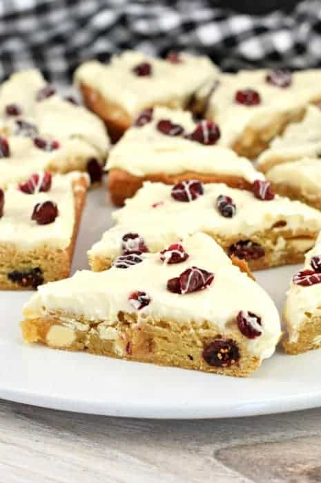 White plate with triangle cut blondies topped with frosting, craisins, and white chocolate drizzle.