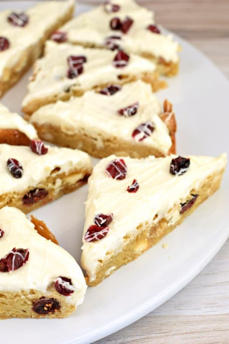 Round white platter with triangle cut blondies topped with cream cheese frosting, craisins, and white chocolate drizzle.