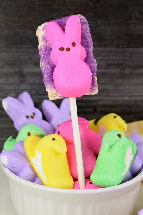 Bowl of marshmallow Peeps and one rice krispie treat on a stick with purple sugar and a pink bunny PEEP.