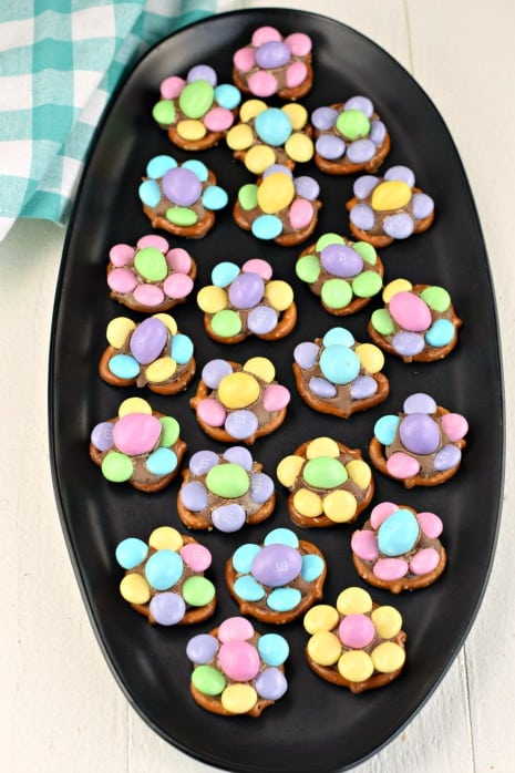 Black oval plate with candy made of pretzel twists, chocolate, and M&M's candies.