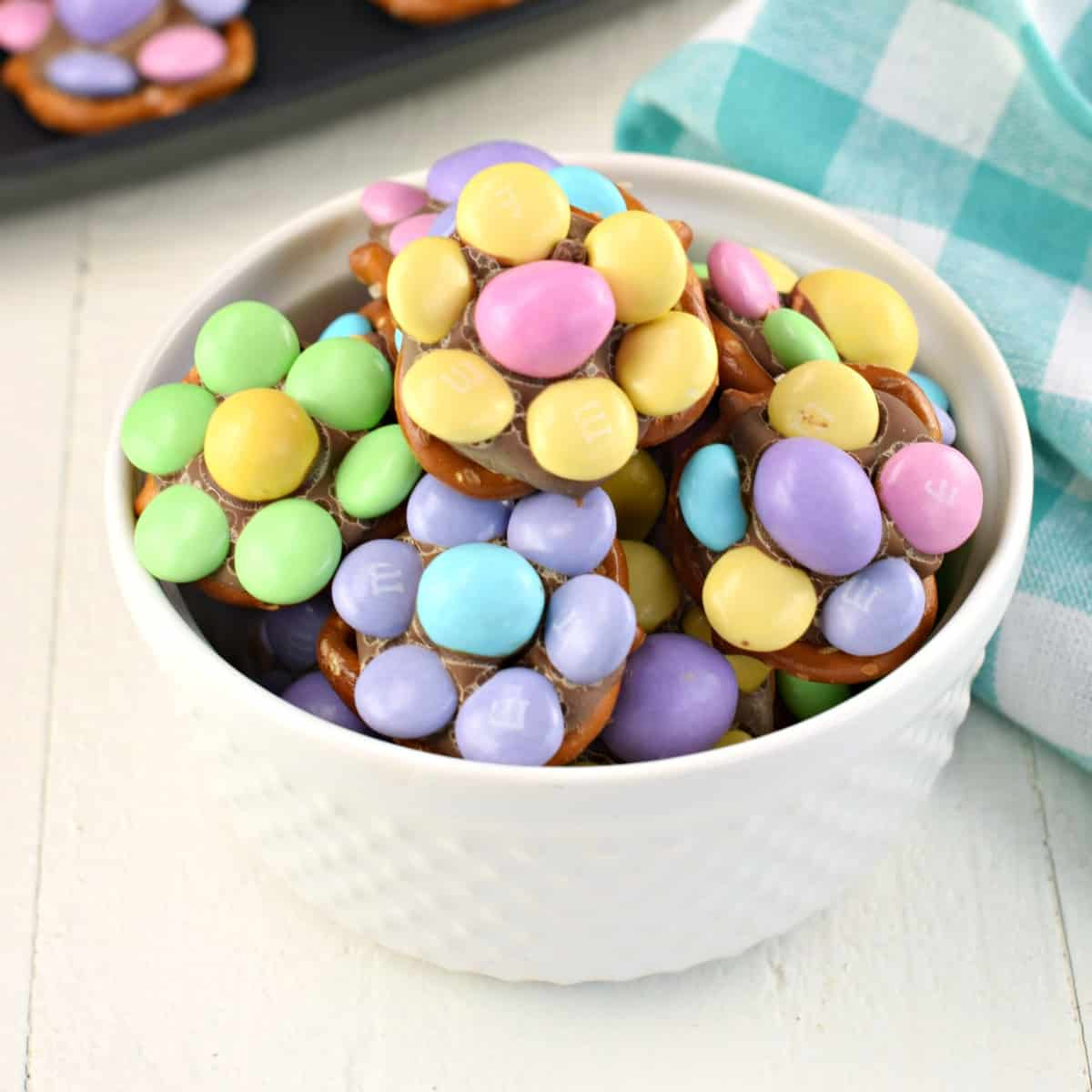 White bowl with pretzel candy topped with chocolate and M&M's.