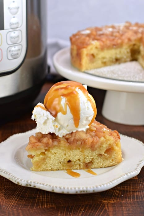 Big slice of apple cake with Instant Pot in background, Slice of apple cake is topped with ice cream and caramel sauce.