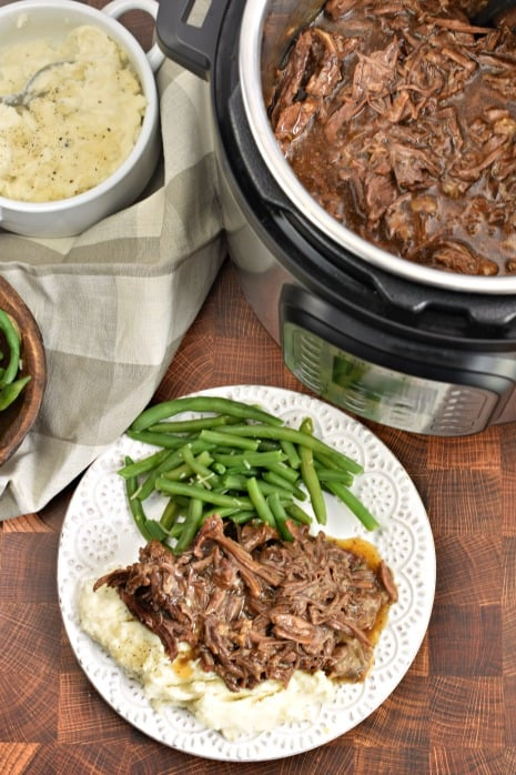 Top view of Instant Pot with balsamic shredded beef, plate with beef, mashed potatoes and green beans.
