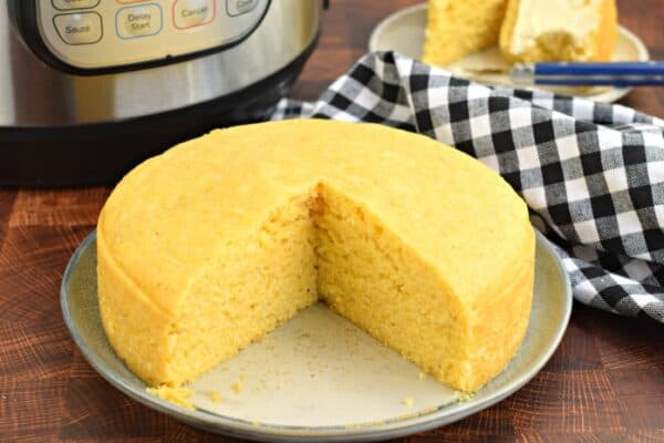 Corn bread on plate with pressure cooker in background.