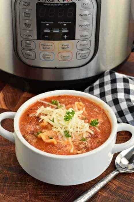 White soup bowl filled with hearty Lasagna Soup and topped with mozzarella cheese. Instant Pot in background.