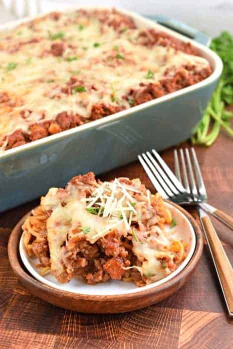 White plate with scoop of baked spaghetti casserole topped with parmesan cheese. Two forks and pan of casserole in background.