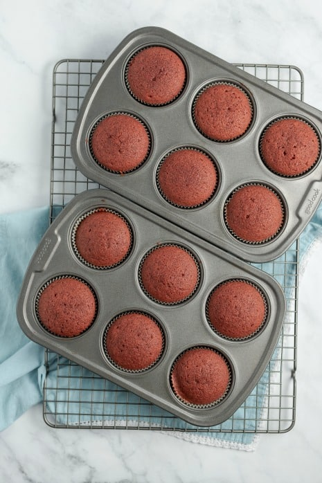 Red velvet cupcakes in two 6-cavity cupcake tins on a wire rack.