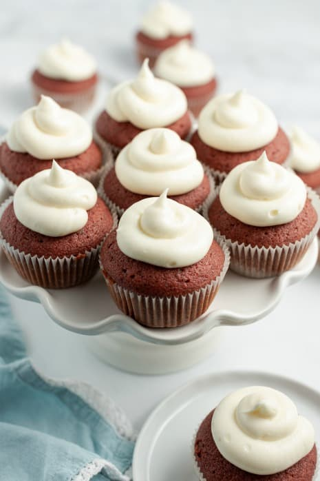Red velvet cupcakes with cream cheese frosting on a scalloped white cake stand.
