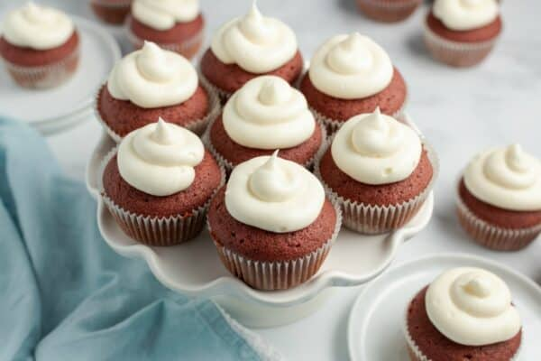 Red velvet cupcakes on a white cake plate with swirls of cream cheese frosting.