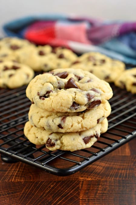 Stack of 3 soft batch chocolate chip cookies on wire cooling rack.
