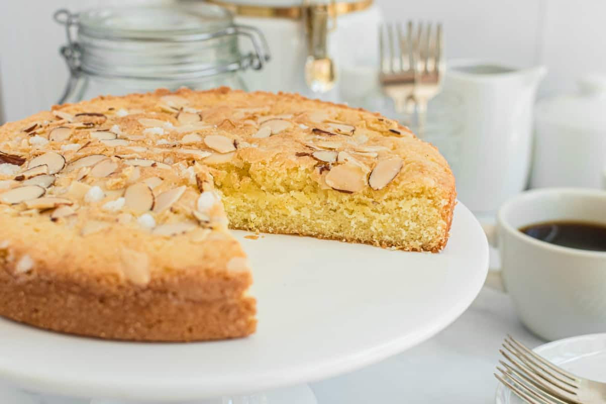 Almond cake on a white cake platter with a slice removed.