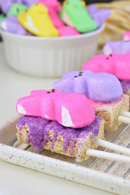 Wire rack with rice krispie treats cut into rectangles with a popsicle stick. Topped with melted white chocolate, purple and pink sprinkles, and marshmallow Peeps.