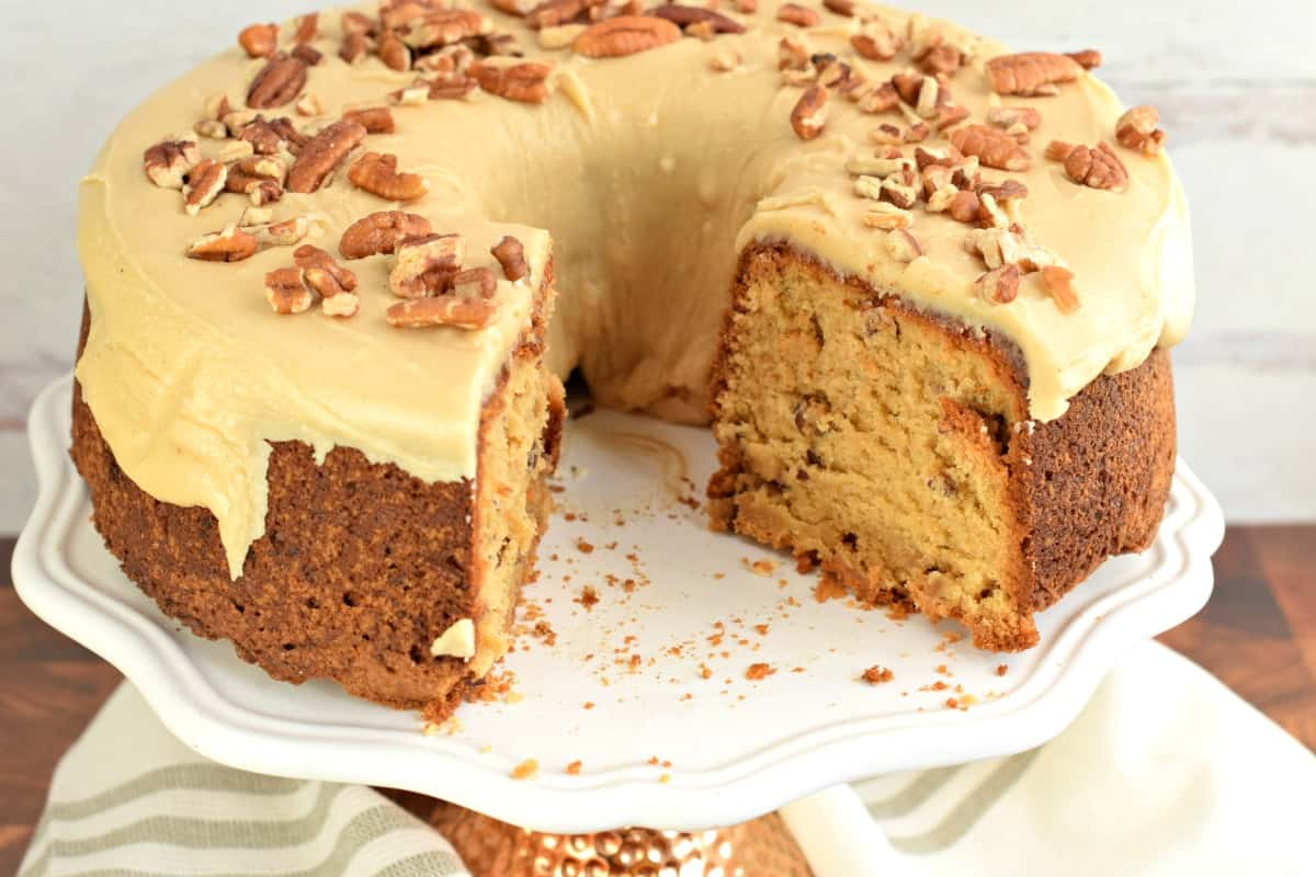 Brown sugar pound cake with caramel glaze on a white cake plate with a big chunk removed.