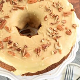 Brown Sugar Pound Cake topped with caramel glaze and pecans on a white cake platter.