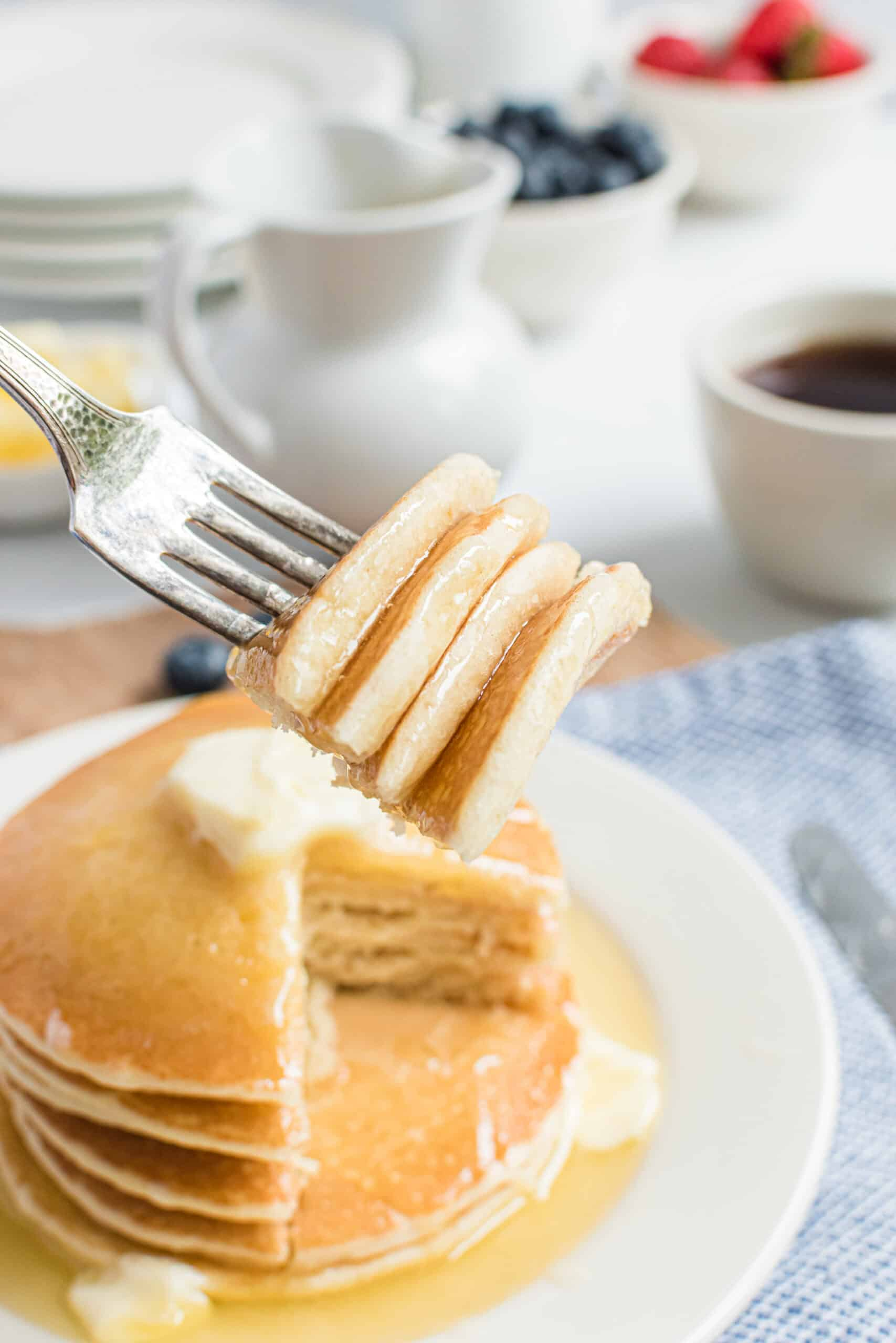 Stack of buttermilk pancakes with a forkful removed.