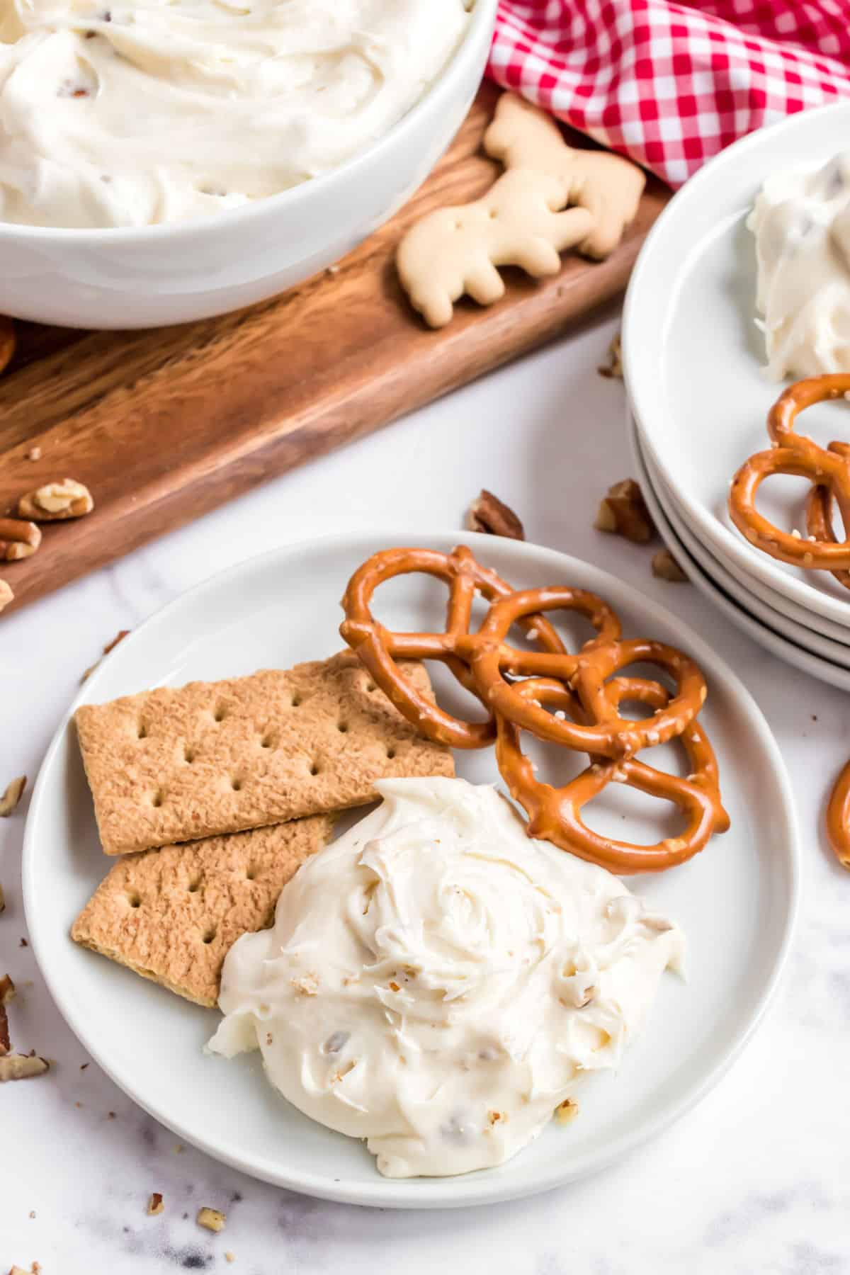 Cheesecake dip scooped onto a white plate with graham crackers and pretzels.