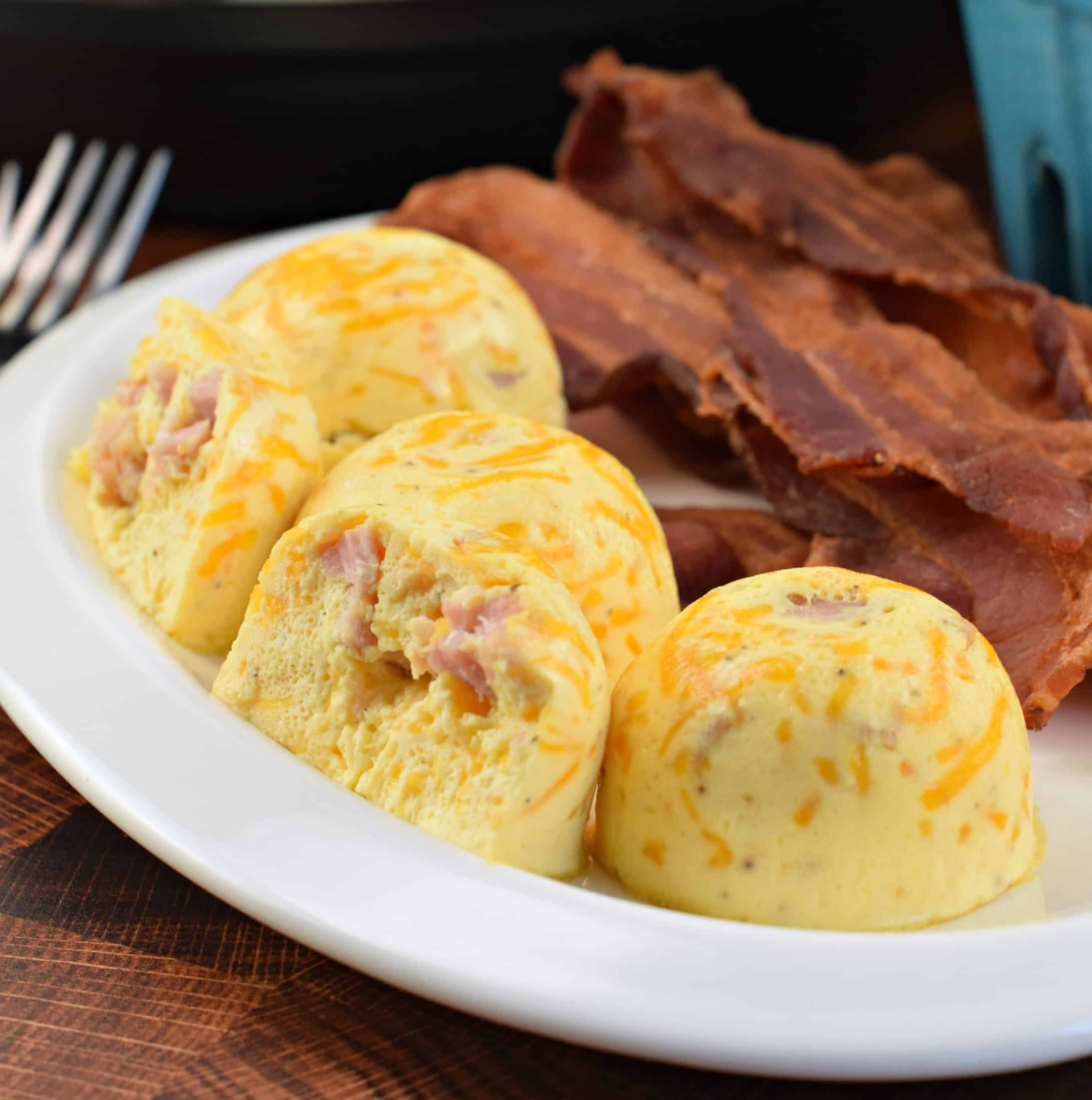 Ham and Cheese egg bites made in the Instant Pot with cooked bacon on a white plate.