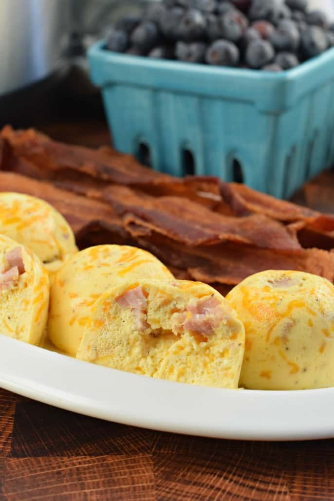 Ham and Cheese Egg bites made in the instant pot on a plate with cooked bacon and a teal bowl full of blueberries.