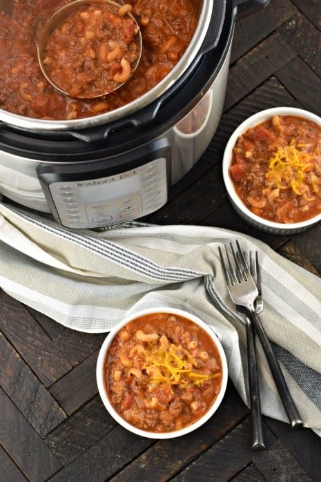 Two bowls of american goulash with Instant Pot filled with more beefy chili mac.