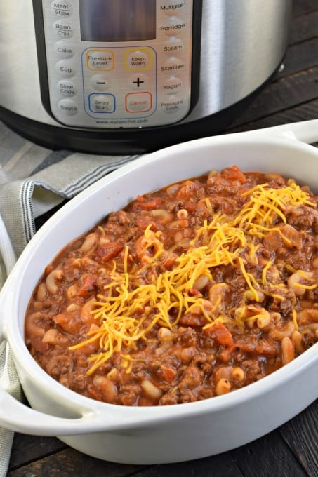Oval white baking dish filled with beefy chili mac with Instant Pot in background.