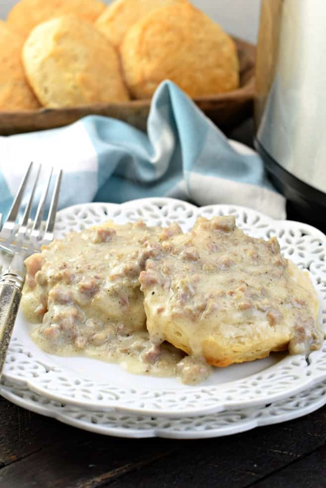 White frilled plate topped with an open faced biscuit and homemade sausage gravy. Tray of extra biscuits in background.
