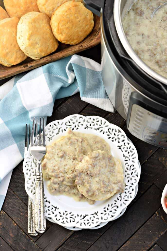 White plate with biscuits and gravy. Instant Pot filled with more sausage gravy, and fresh baked biscuits in a wooden bowl.