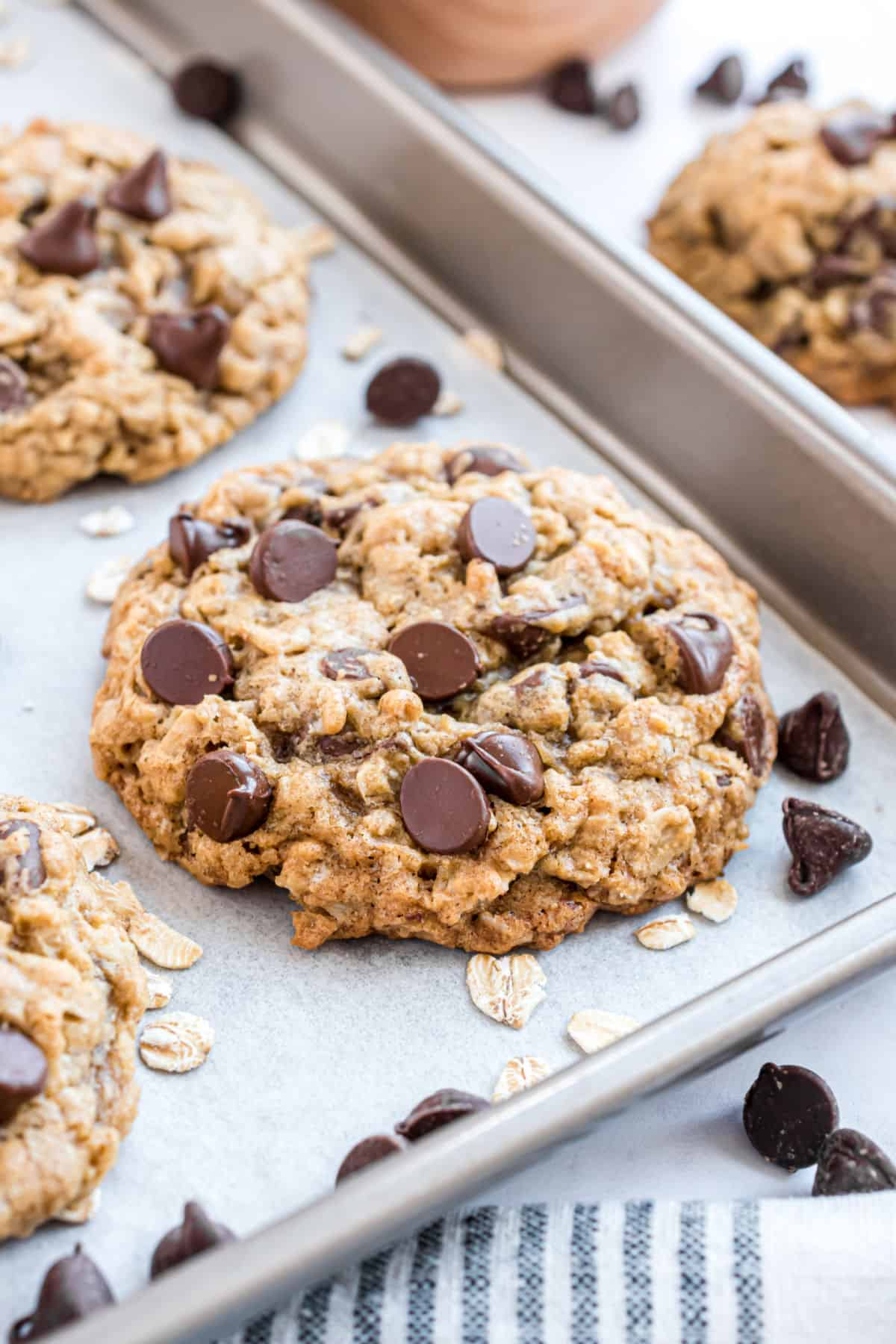 Oatmeal chocolate chip cookie baked on a parchment paper lined cookie sheet.