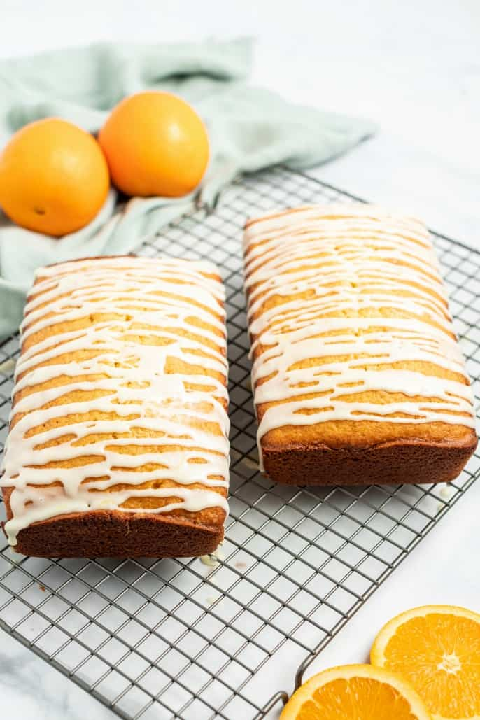 2 loaves of glazed orange bread on a wire rack with two oranges in background.