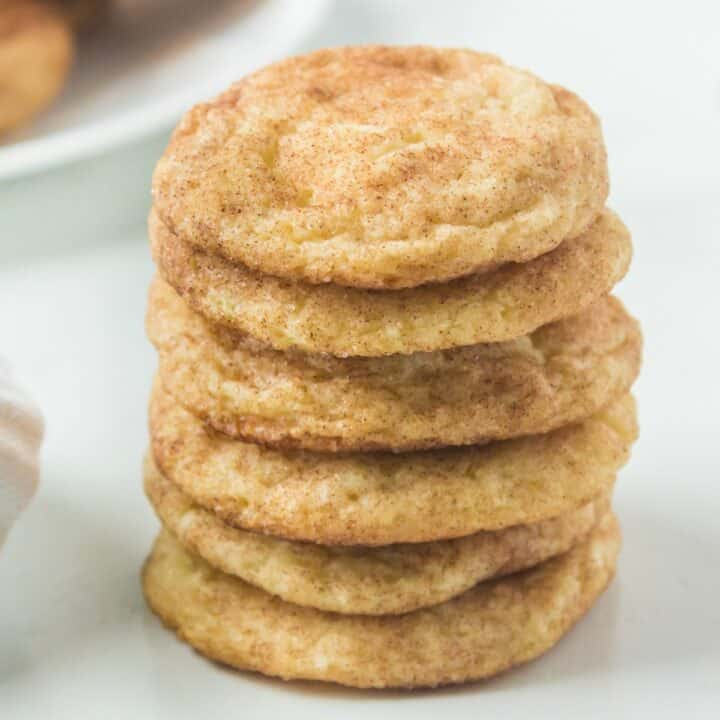 Stack of six snickerdoodle cookies on white table.