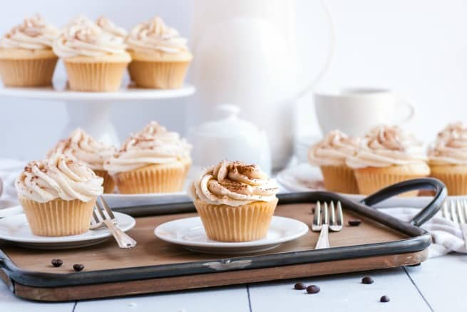 Wooden tray with tiramisu cupcakes on it and behind it.