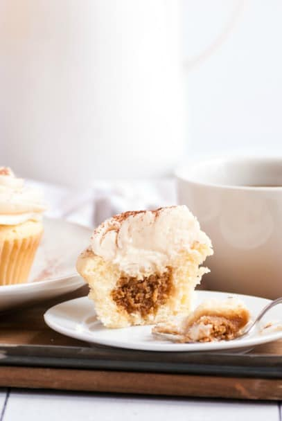 Vanilla cupcake with espresso filling and frosting broken in half to see the filling.