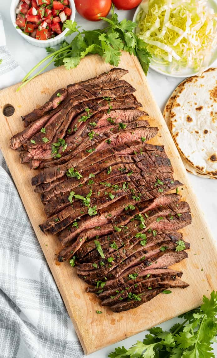 Grilled flank steak sliced thin on a wooden cutting board and sprinkled with chopped cilantro.