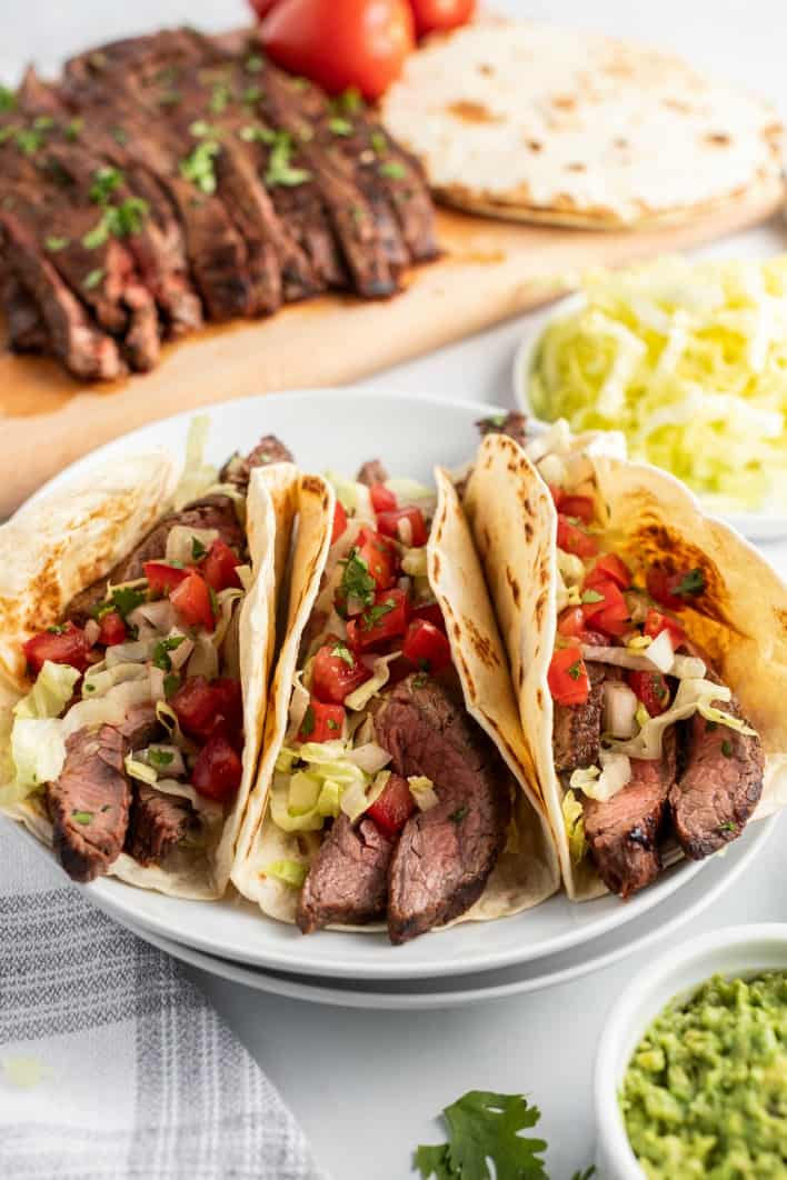 3 flour tacos topped with carne asada, pico de gallo, lettuce, and cilantro. Served on a white plate with a bowl of guacamole.