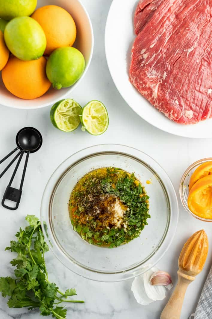 Ingredients needed for carne asada, including flank steak, limes, oranges, and cilantro.