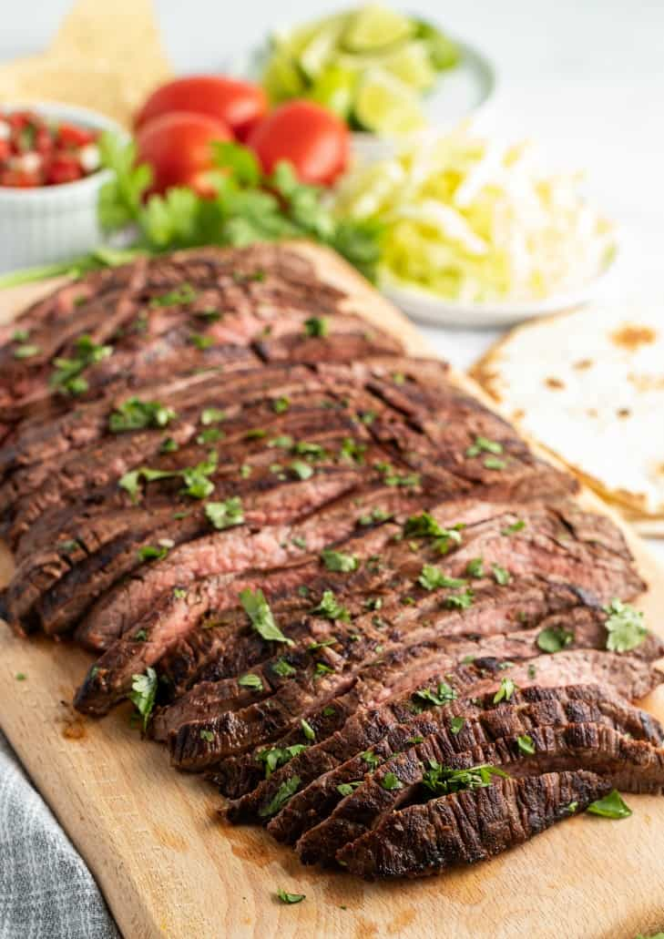 Grilled carne asada (flank steak) on a wooden cutting board with all the fixings on the side.