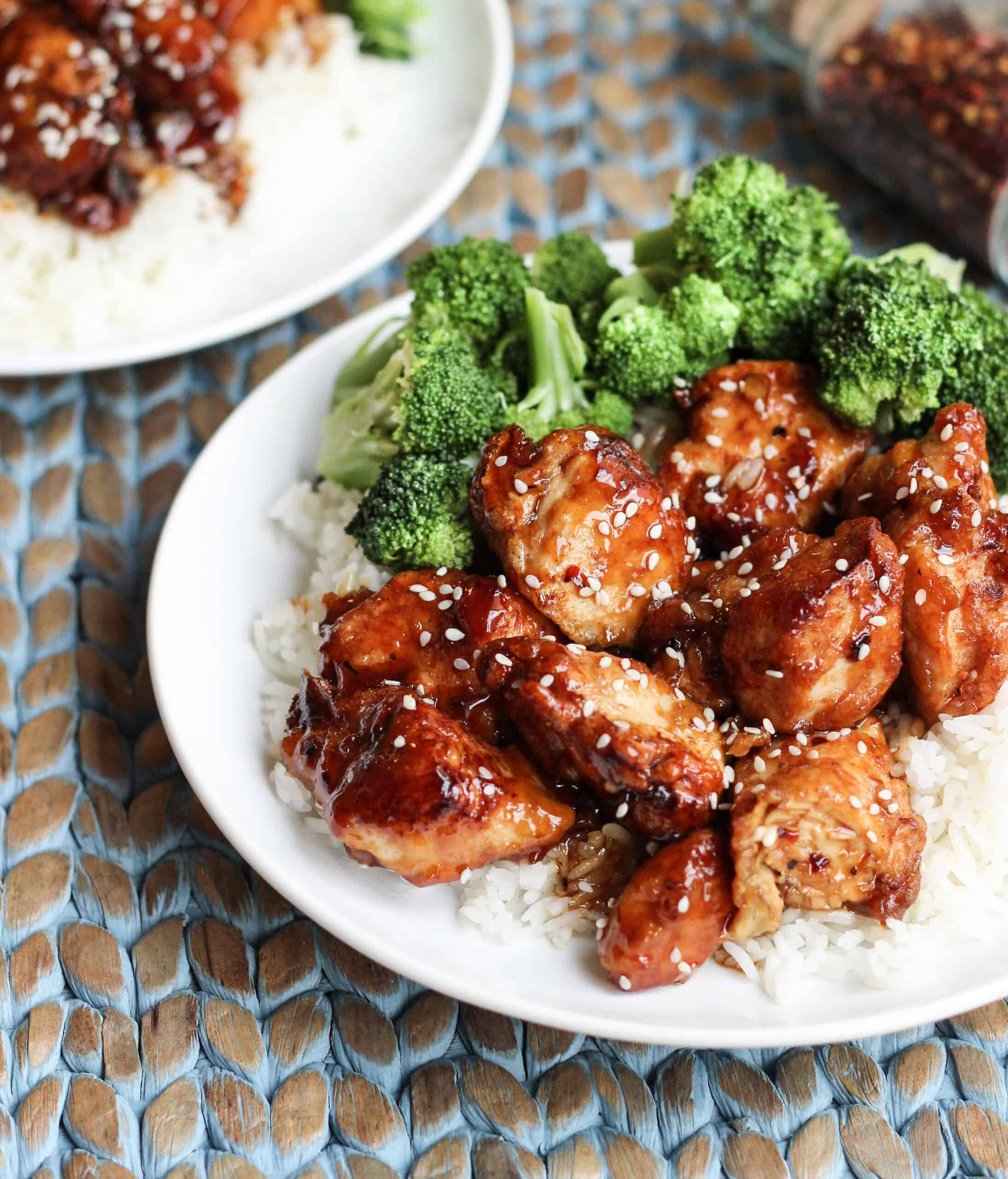 White dinner plate with white rice and glazed sesame seed chicken and broccoli.