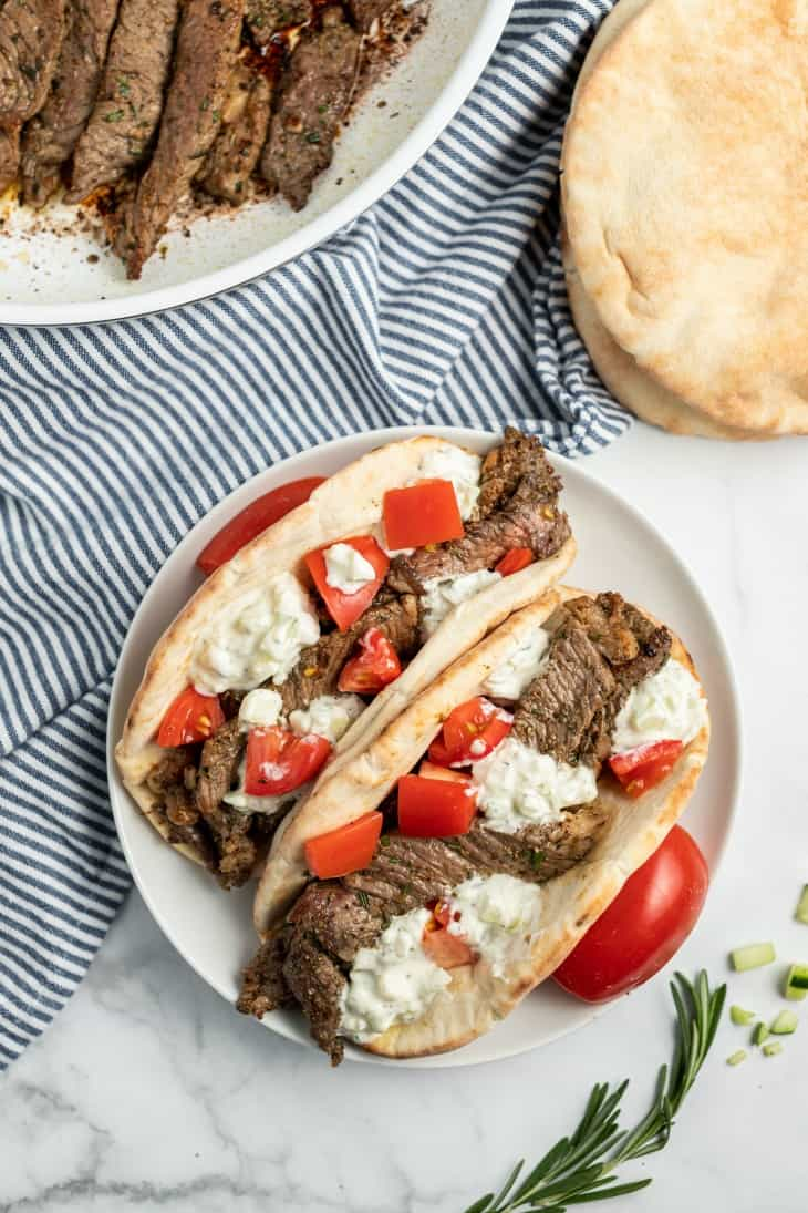Two pitas on a white plate with greek seasoned sirloin steak, tomatoes, and cucumber sauce.