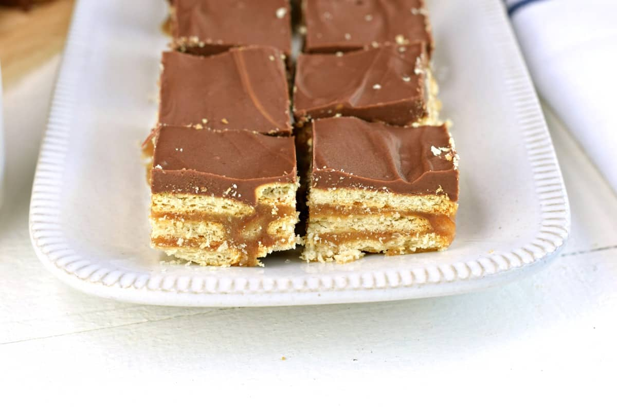Rectangle white platter with cracker bars cut into squares and topped with chocolate.