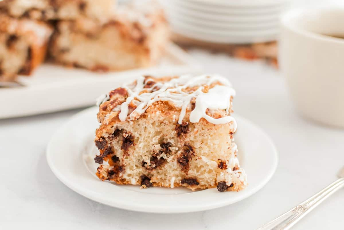 Slice of chocolate chip coffee cake with vanilla glaze on a white plate.