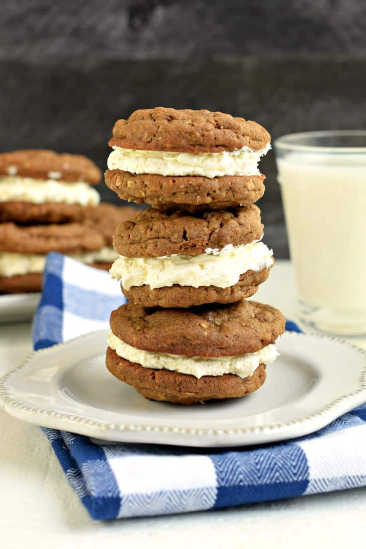 Stack of 3 chocolate oatmeal cream pies on a white plate with blue and white checkered napkin.