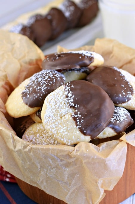 Wooden bowl with parchment paper filled with chocolate dipped potato chip cookies.