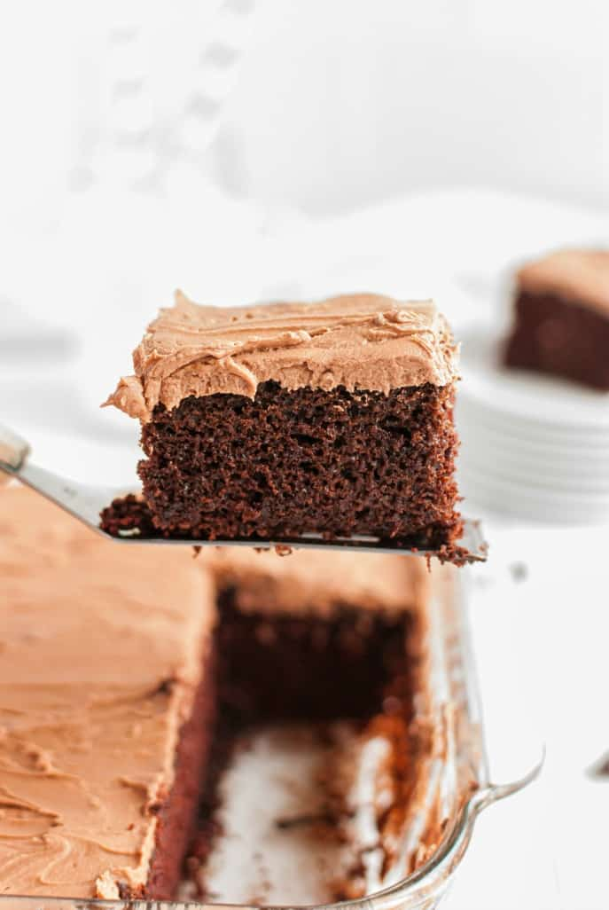 Slice of chocolate cake with chocolate frosting on a spatula being lifted out of the cake pan.