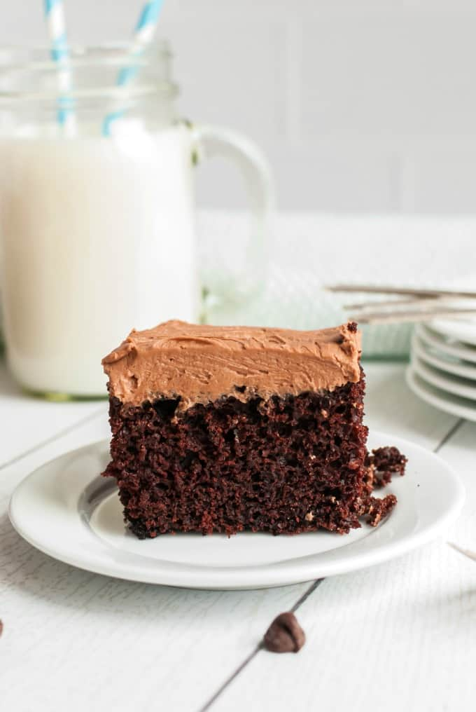 Chocolate frosted wacky cake on a white plate with a mug of milk.