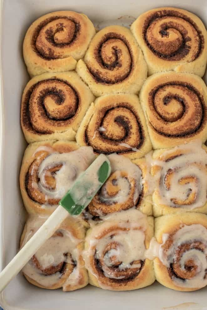 Baking cinnamon rolls being frosted with cream cheese icing.