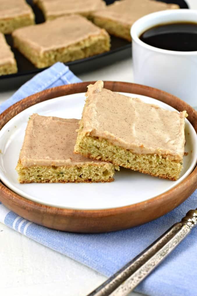 Two slices of zucchini bars with cinnamon frosting on a white plate.