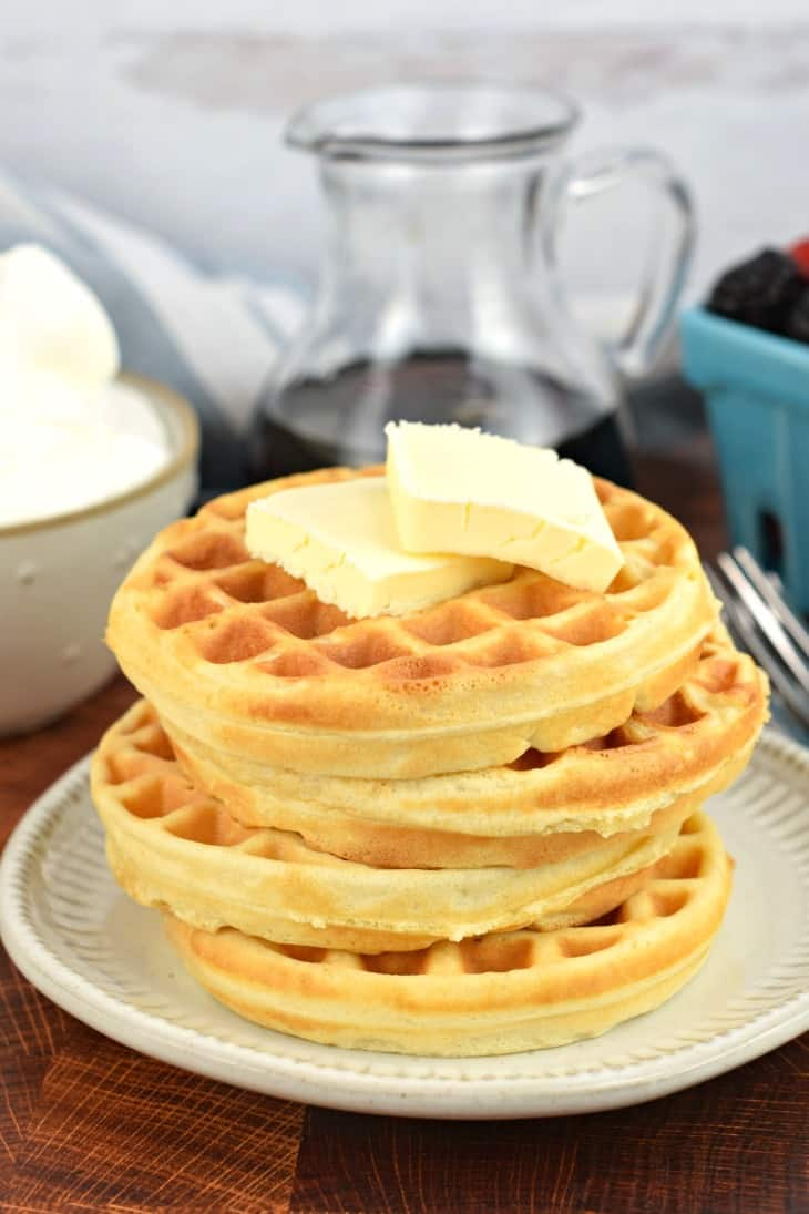 Stack of fresh cooked homemade waffles with two pats of butter. No toppings.