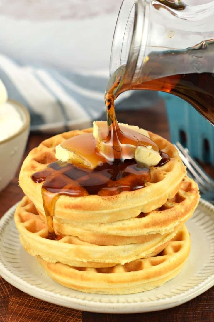 Stack of four waffles with maple syrup being poured over the top.