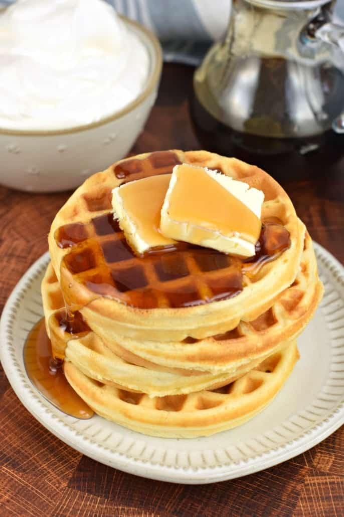 Stack of 4 waffles, two pats of butter and maple syrup drizzled on top.