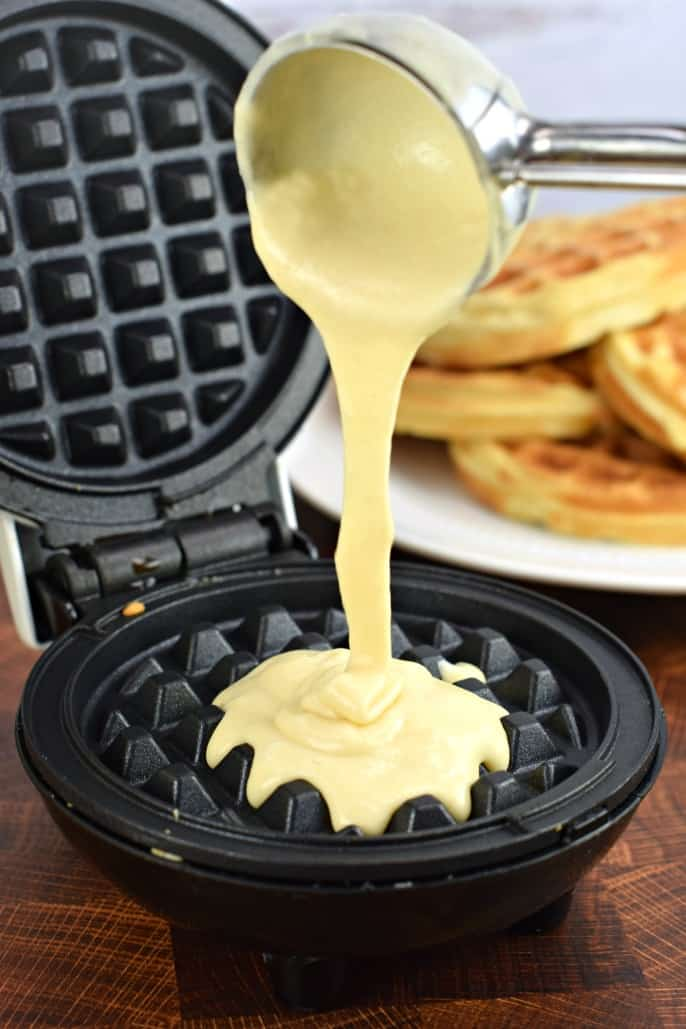 Metal scoop pouring batter onto a waffle iron.