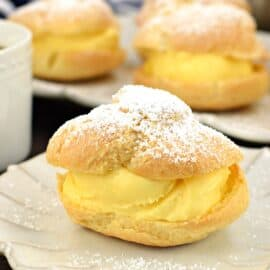 Cream puff on a white plate filled with custard and topped with powdered sugar.